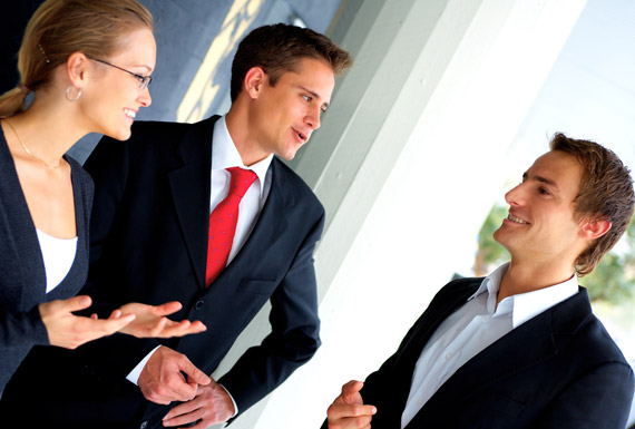 two men in suits and lady in suit smiling and talking